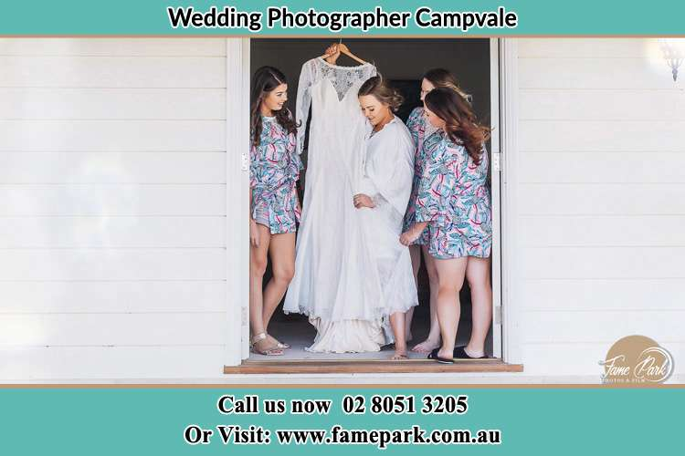 Photo of the Bride and the bridesmaids checking the wedding gown at the front door Campvale NSW 2318