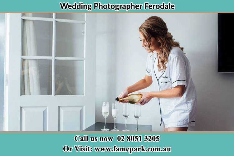 Photo of the Bride pouring wine on the glasses Ferodale NSW 2318