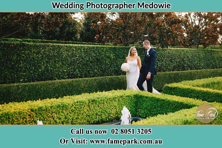 Photo of the Bride and the Groom walking at the garden Medowie NSW 2318