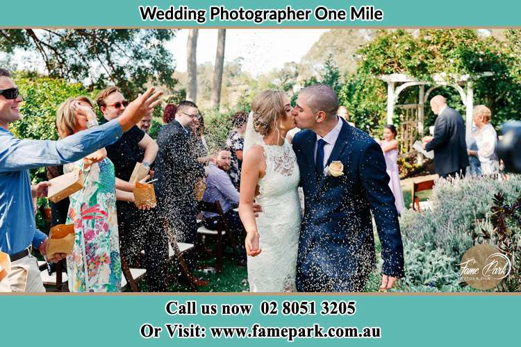 Photo of the Bride and the Groom kissing while showering rice by the visitors One Mile NSW 2316