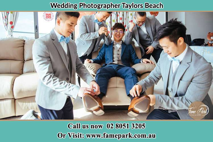 Photo of the Groom helping by the groomsmen getting ready Taylors Beach NSW 2316