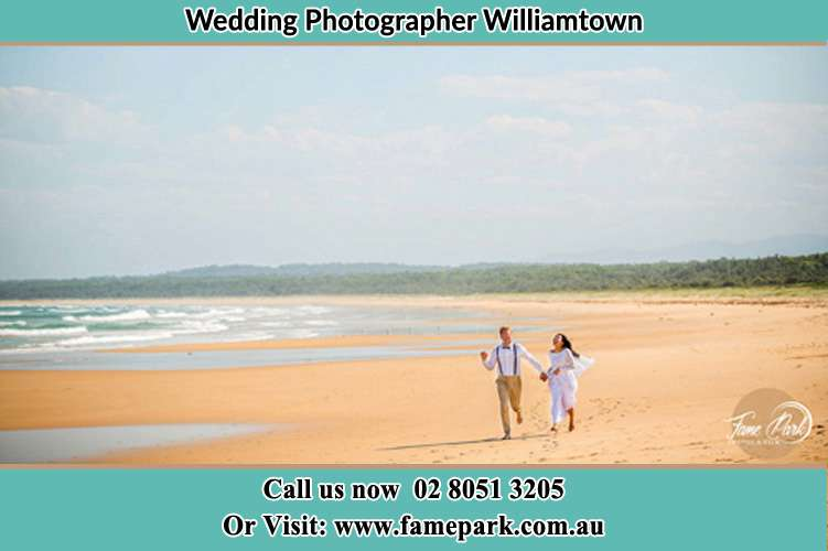 Photo of the Groom and the Bride walking at the sea shores Williamtown NSW 2318
